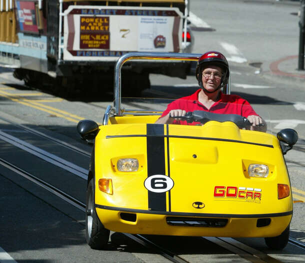 Tom Ruddick of Muncie, Indiana, drives up Hyde Street in a GoCar motorized cart, one of eight that have become big hits with tourists and San Francisco natives alike. The new SF company called GoCar Rentals is renting two-seat moped cars equipped with a Global Positioning System giving tourists an automated talking guided tour of SF. The company uses a Trigger Scooter Car, a bright yellow three-wheeled vehicle that looks like a golf cart  Photo taken on 04/29/04 in San Francisco, Ca.