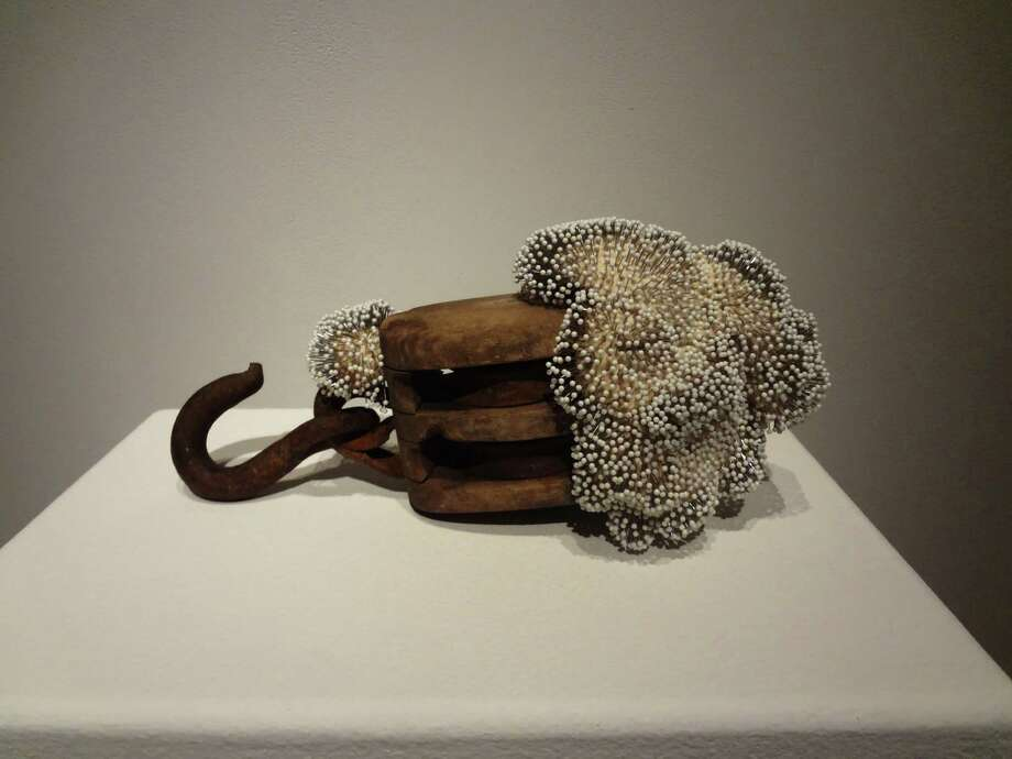 """For """"Pulley,"""" San Antonio artist Dyan Green created delicate patterns on an antique pulley with white-balled straight pins. Photo: Photo By Steve Bennett /Photo By Steve Bennett"""