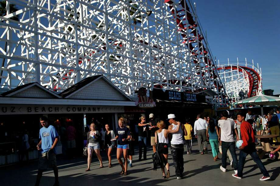 People enjoy the Santa Cruz Beach Boardwalk as the Giant Dipper wooden roller coaster looms above in Santa Cruz, Calif., on Wednesday, July 30, 2014. It's over 90 years old and is a National Historic Monument. Photo: Preston Gannaway / Special To The Chronicle / ONLINE_YES