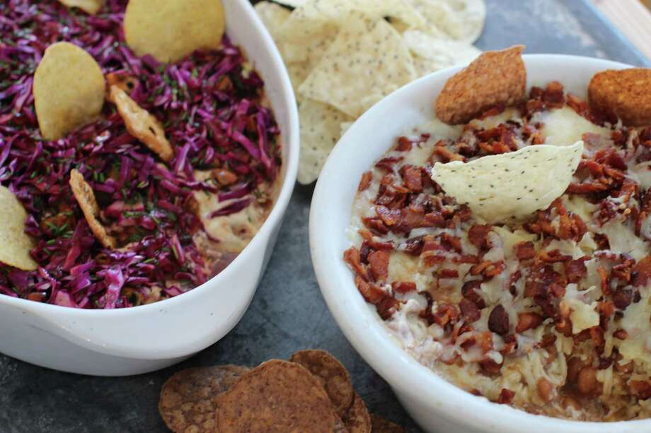 This Jan. 26, 2015 photo shows the Seattle super seven dip, left, and New England super seven dip in Concord, N.H. The Seattle dip is made with teriyaki-seasoned Dungeness crabmeat, creamy cheese, caramelized onions, smoked mussels, purple cabbage slaw and blackberry vinaigrette. The New England dip is made with barbecued pulled pork topped with skillet sauteed apples and butter. (AP Photo/Matthew Mead) ORG XMIT: MER2015012616395308 Photo: Matthew Mead / FR170582 AP