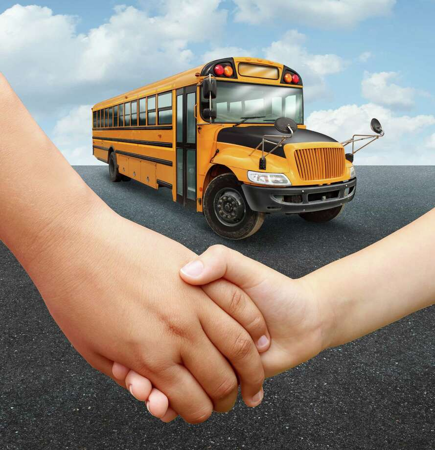 School children bus with two young students of elementary age holding hands preparing to go into the yellow transport vehicle as an education and learning concept. / freshidea - Fotolia