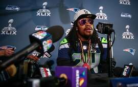 Marshawn Lynch sits at a microphone during Super Bowl XLIX media interviews on Wednesday, January 28, 2015 at the team's hotel in Phoenix, Arizona.