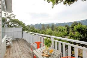 The top-level deck overlooks neighboring homes and evergreens.