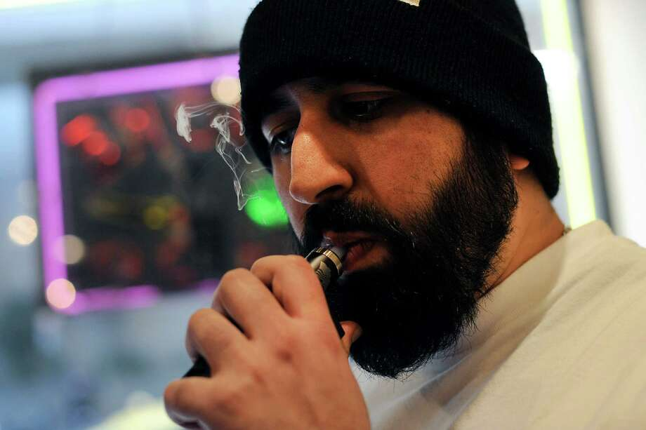 Owner Feras Kalieh smokes an e-cigarette while working at Vapor Smoke Shop in San Francisco in December. Photo: Michael Short / Special To The Chronicle / ONLINE_YES
