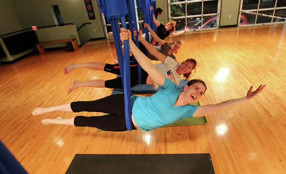 Yoga instructor Anne McCarthy leads students in an aerial yoga class at Synergy Studios earlier this year. Aerial yoga allows practitioners to develop strength and flexibility in a way they cannot always attain with yoga performed on the ground. Photo: Kin Man Hui /San Antonio Express-News / ©2015 San Antonio Express-News
