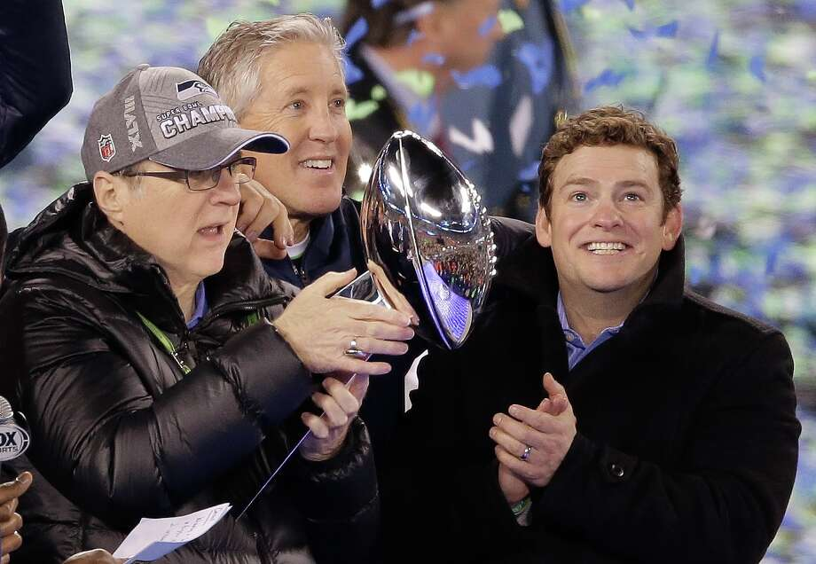 When the Seahawks celebrated their Super Bowl victory last year, general manager John Schneider, right, was the low-profile figure compared to owner Paul Allen, left, a billionaire businessman, and Pete Carroll, one of the most visible coaches in football over the last 15 years. Photo: Charlie Riedel, STF / AP