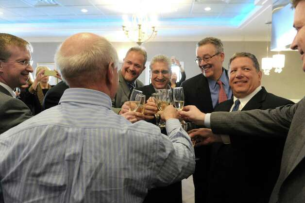 Angelo Mazzone, right, shares a Champagne toast with guest during an unveiling of new headquarters and catering center of Mazzone Hospitality on Wednesday Jan. 27, 2015 in Clifton Park , N.Y. (Michael P. Farrell/Times Union) Photo: Michael P. Farrell / 00030364A