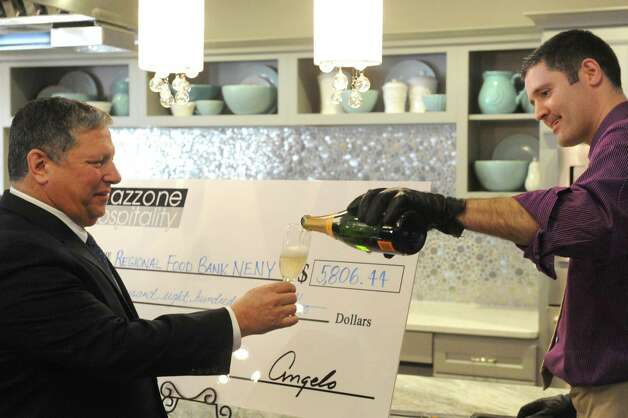 Angelo Mazzone, left, is poured some champange by Matt Consolo with MoA«t Hennessy during an unveiling of new headquarters and catering center of Mazzone Hospitality on Wednesday Jan. 27, 2015 in Clifton Park , N.Y. Mazzone Hospitality also made a $5,806.44 donation to the Regional Food Bank of NorthEast New York .(Michael P. Farrell/Times Union) Photo: Michael P. Farrell / 00030364A