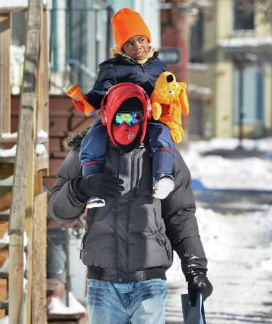 Howard Dave Johnson of Albany and his son Davion Johnson, 3, brave a sunny but cold morning walk up Henry Johnson Blvd. Wednesday Jan. 28, 2015, in Albany, NY.  (John Carl D'Annibale / Times Union) Photo: John Carl D'Annibale