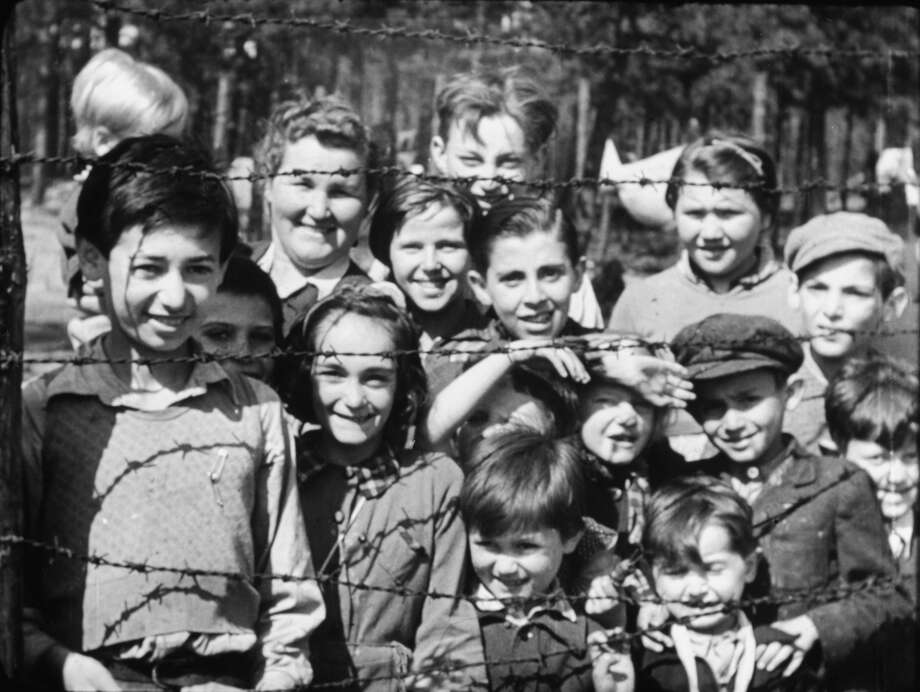 Smiling children through barbed wire taken by Sgt Lewis, Photo: Courtesy, German Concentration Camps Factu