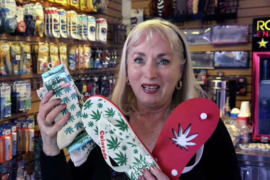 """In this Jan. 27, 2015 photo, former school teacher and current souvenir entrepreneur Ann Jordan displays a few of her products, socks and flip-flops decorated with marijuana-themes, as she drops off supplies to one of her sellers, the Red Carpet Car Wash and Detailing, in Aurora, Colo. Marijuana is legal in Colorado, but not at its largest airport - and now Denver International Airport wants to keep out weed-themed souvenirs, too. A policy enacted this month bans the sale of souvenirs depicting marijuana leaves or Colorado's ubiquitous """"Mile High"""" pot puns. (AP Photo/Brennan Linsley) Photo: Brennan Linsley, STF / AP"""