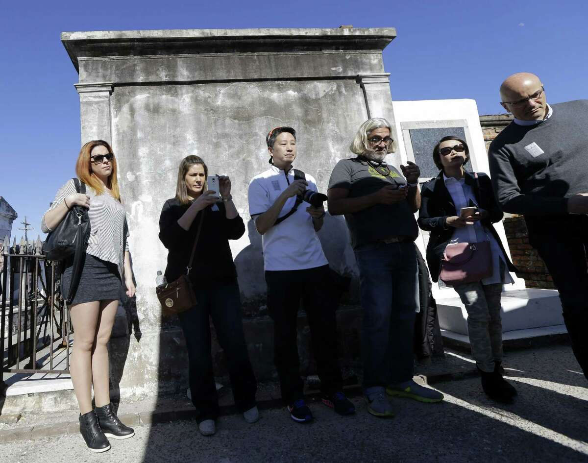 Visitors take photos of the tomb of Marie Laveau inside St. Louis Cemetery No. 1 in New Orleans, Tuesday, Jan. 27, 2015. The historic New Orleans cemetery that may have started the city's tradition of above-ground crypts will soon be off-limits to tourists on their own because of repeated vandalism among the tombs, the Roman Catholic archdiocese that owns the property has announced. Starting in March, entry to St. Louis Cemetery No. 1 and its labyrinth of mausoleums will be restricted to the relatives of the dead buried there and to tourists whose guide is registered with the Archdiocese of New Orleans. (AP Photo/Gerald Herbert)