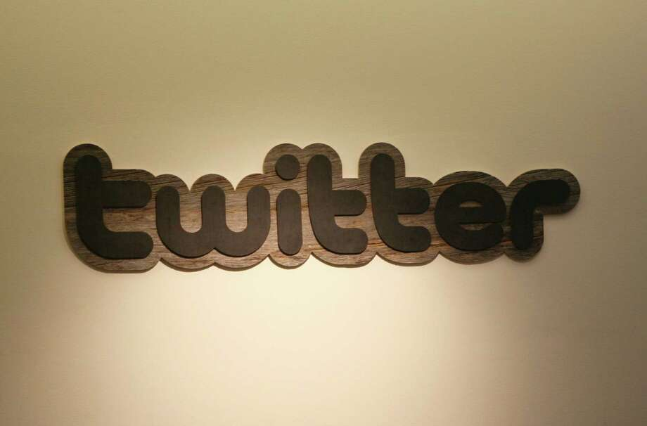 """(FILES) This March 11, 2011 file photo shows theTwitter logo displayed at the entrance of Twitter headquarters in San Francisco,California. Twitter on January 27, 2015 began rolling out new group chat and video features as it worked to ramp up use of the one-to-many messaging service. """"Private conversations on Twitter are a great complement to the largely public experience on the platform,"""" product director Jinen Kamdar, whose handle is @jinen, said in an online post. """"The group function lets you start conversations with any of your followers and they don't all need to follow one another in order to chat."""" Twitter allows users to send direct messages to one another; the new feature expands that capability to allow shared exchanges involving as many as 20 people, according to Kamdar. AFP PHOTO/KIMIHIRO HOSHINO / FILESKIMIHIRO HOSHINO/AFP/Getty Images Photo: KIMIHIRO HOSHINO / AFP / Getty Images / AFP"""