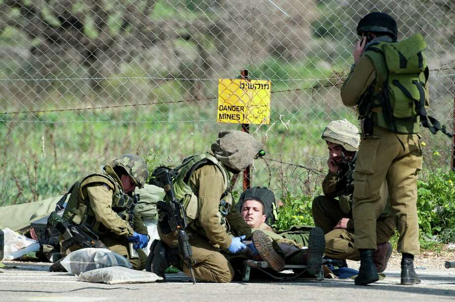 Israeli soldiers treat a wounded soldier near the Israel-Lebanon border, Wednesday, Jan. 28, 2015. A missile fired by the Lebanese Hezbollah group struck an Israeli military convoy on Wednesday, killing two soldiers in an apparent retaliation for a deadly airstrike attributed to Israel that killed many Hezbollah fighters in Syria earlier this month. The violence was the deadliest Hezbollah attack on Israel since a 2006 war between the two sides. (AP Photo/Gili Eliyahu, Jinipix) Photo: Gili Eliyahu, STR / Jinipix