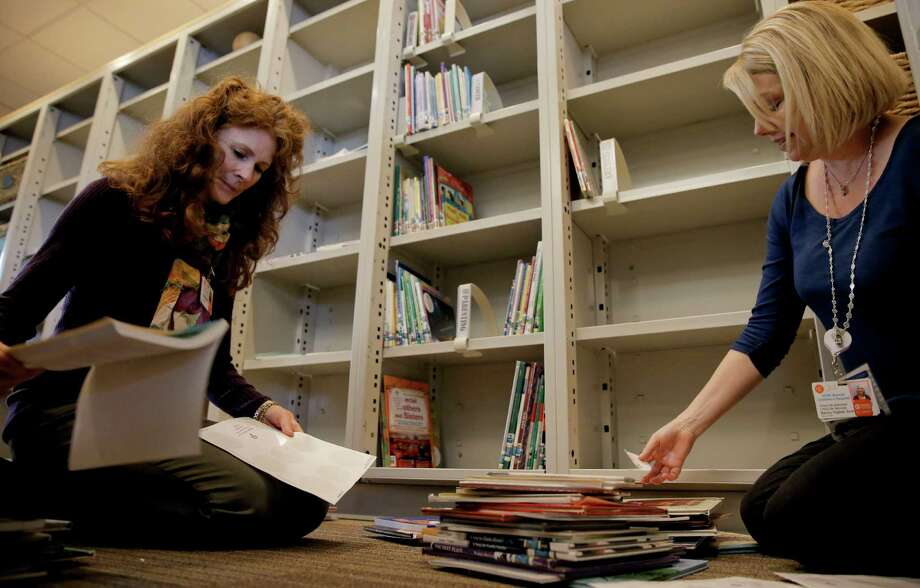 Lisa Lee (left) and Becky Higbee get the Center for Families room stocked up with books as the UCSF Medical Center at Mission Bay that's slated to open over the weekend. Photo: Michael Macor / The Chronicle / ONLINE_YES