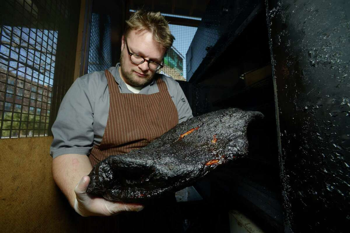 Chef Tim Rattray pulls a brisket from the smoker at The Granary.