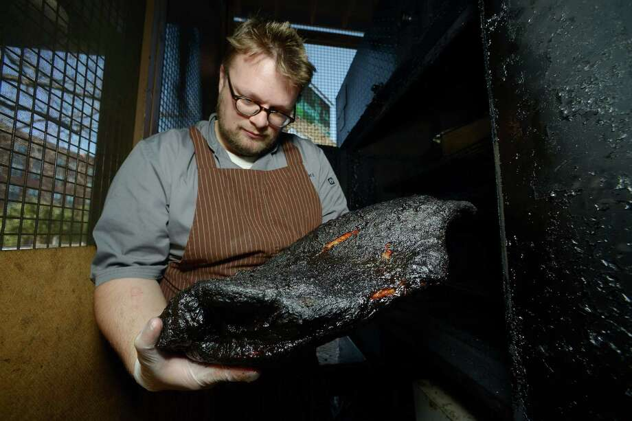 Chef Tim Rattray pulls a brisket from the smoker at The Granary. Photo: Billy Calzada /San Antonio Express-News /  San Antonio Express-News