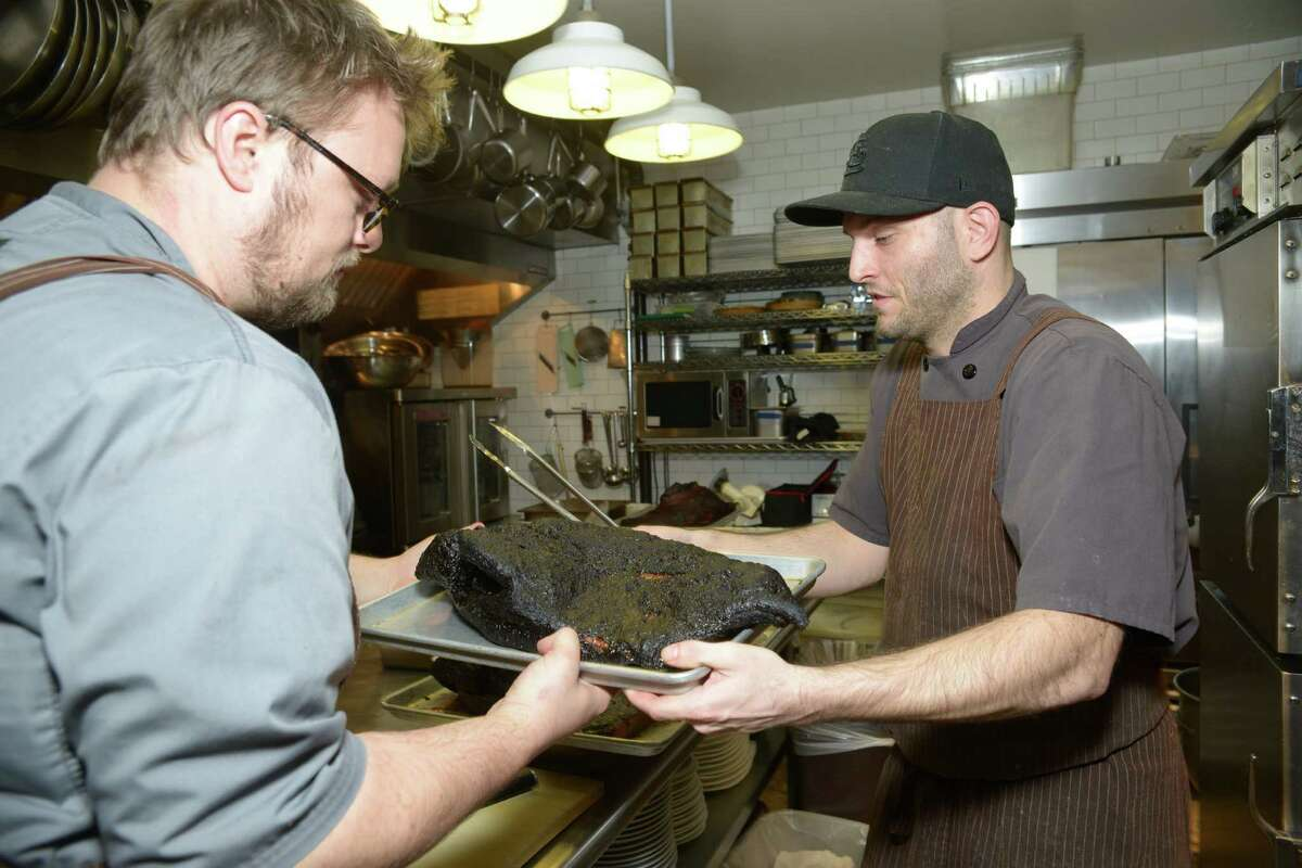 Chef Tim Rattray, left, and Mike Grimes handle a brisket from the smoker at The Granary.