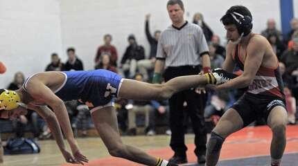 Danbury's Jakob Camacho, right, tries to drag Newtown's  Tom Leuci back into the ring as they wrestle in the 106 pound weight class during a high school wrestling dual meet on Wednesday, January 28, 2015, at Danbury High School, Danbury, Conn.