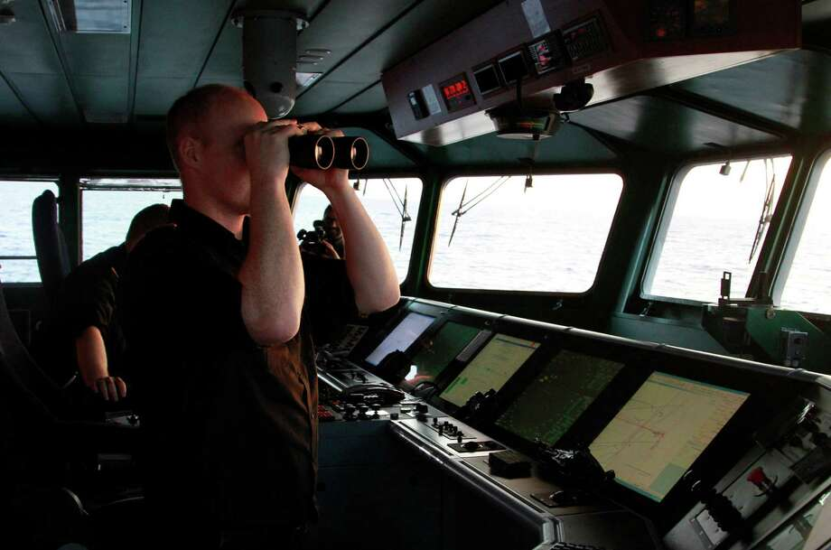 In a photo taken earlier this month, a crewman on the Icelandic Coast Guard ship Tyr scans the waters between Greece and Italy as part of the 19-nation Operation Triton, patrolling in search of Syria and Iraqi migrants trying to reach Europe. Photo: Paul Schemm, STF / AP