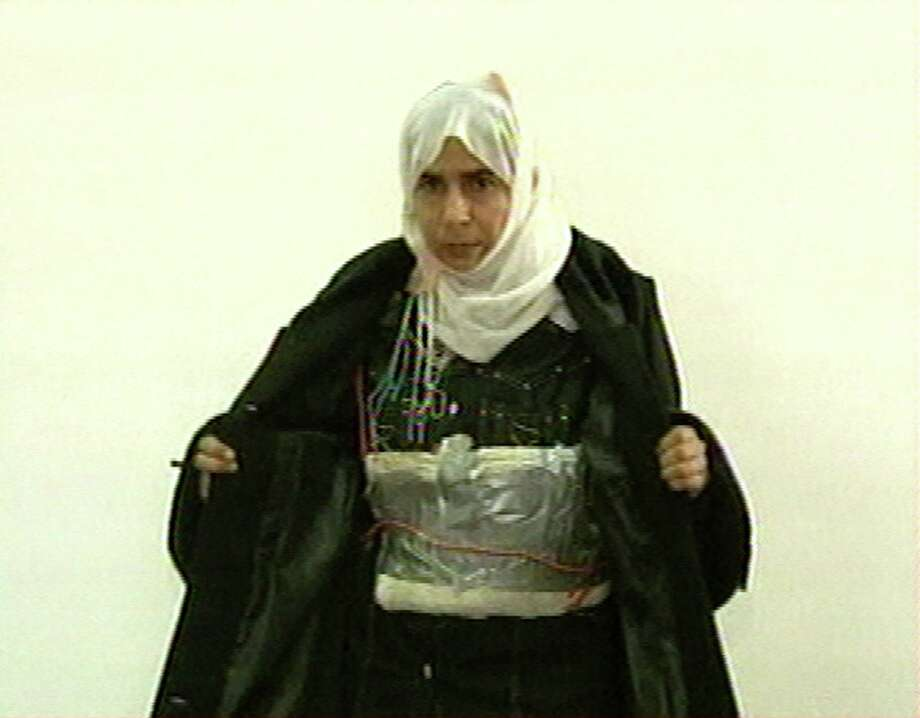 Jordanian prisoner Sajida al-Rishawi, an Iraqi woman, is shown with the explosive belt that failed to detonate in a 2005 attack. Her release is being sought by Islamic militants.  Photo: Anonymous, HONS / JORDANIAN TV