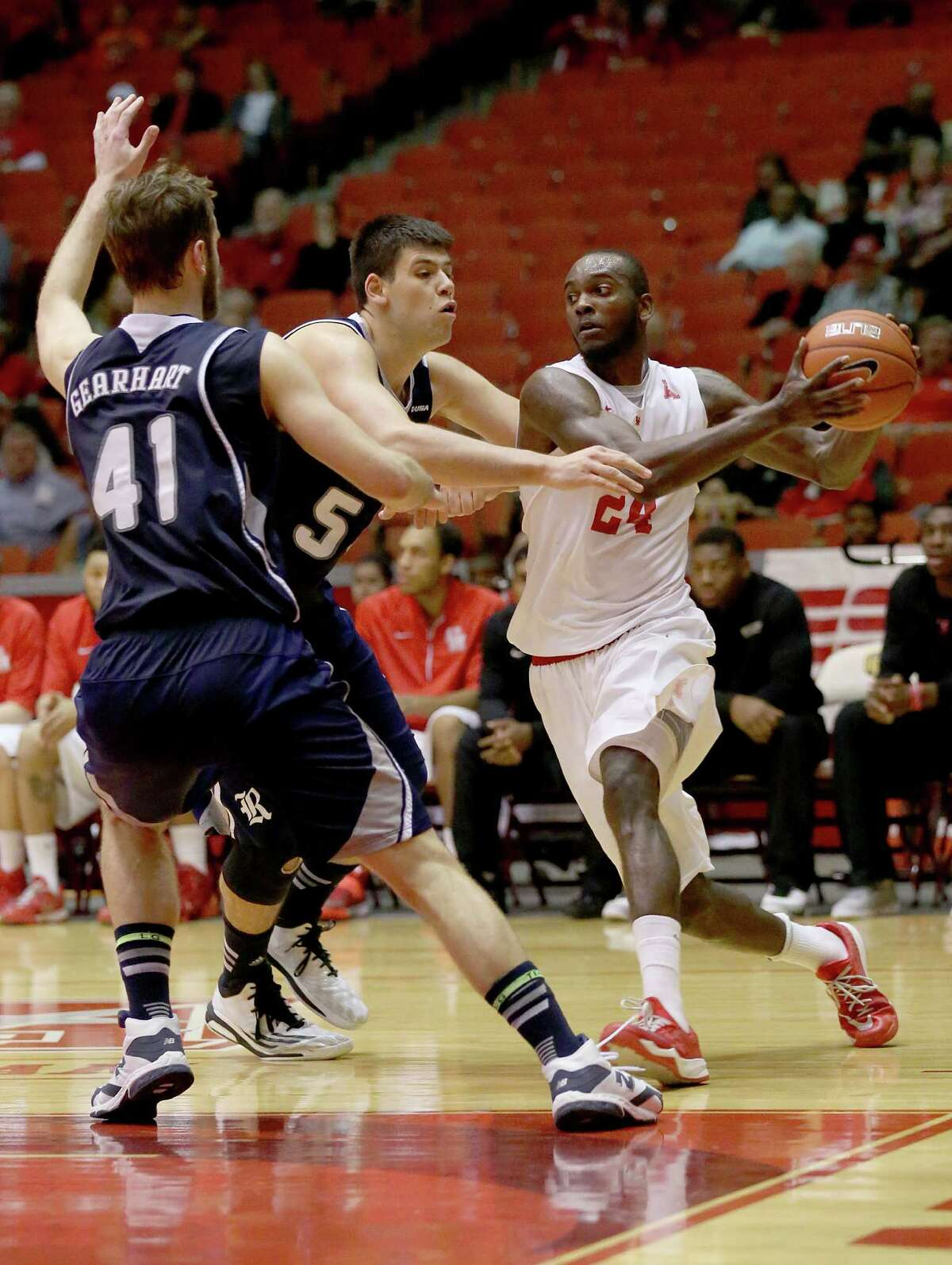 Houston Cougars forward Devonta Pollard (24) drives against Rice Owls forward Seth Gearhart (41) and center Andrew Drone (54) in the second half in a NCAA basketball game on Wednesday, January 28, 2015 at Hofheinz Pavilion in Houston, TX. UH won 59 to 48 .