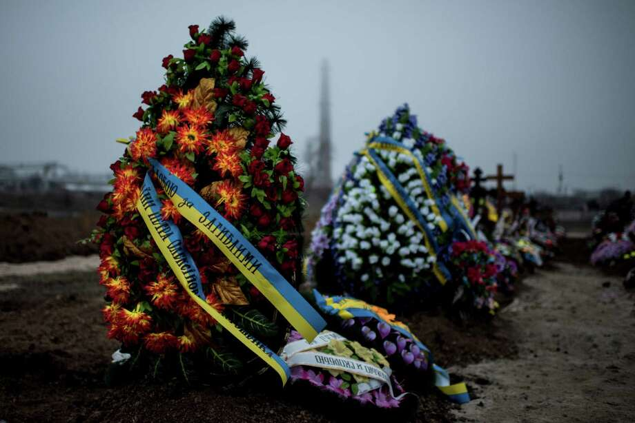 """Wreaths are placed on the graves of victims of Saturday's shelling after a funeral in Mariupol, Ukraine, Tuesday Jan. 27, 2015. European Union leaders are threatening fresh sanctions against Russia because of what it sees as """"growing support"""" of Moscow for separatists in eastern Ukraine during intensified fighting over the past days. (AP Photo/Evgeniy Maloletka) ORG XMIT: MOSB125 Photo: Evgeniy Maloletka / AP"""