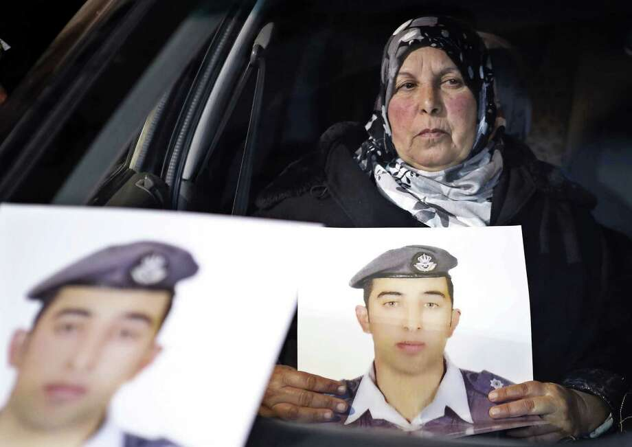 In this Tuesday, Jan. 27, 2015 photo, a woman holds a picture of her son, Jordanian pilot Lt. Mu'ath al-Kaseasbeh, who is held by Islamic State group militants, in a car during a sit-in in front of the cabinet offices in Amman calling for his release, hours after militants posted a video purporting to show a Japanese hostage holding his picture with a message that both hostages would be killed within 24 hours. (AP Photo/Raad Adayleh) ORG XMIT: RA109 Photo: Raad Adayleh / AP