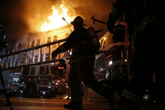 San Francisco Fire Department members fight blaze at 22nd and Mission Street in San Francisco, Calif., on Wednesday, January 28, 2015.