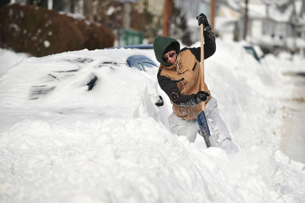 Alex Williams tries to clear snow from her buried car after a winter storm, Wednesday, Jan. 28, 2015, in New London, Conn. The storm buried the Boston area in more than 2 feet of snow and lashed it with howling winds that exceeded 70 mph. (AP Photo/The Hartford Courant, Cloe Poisson)