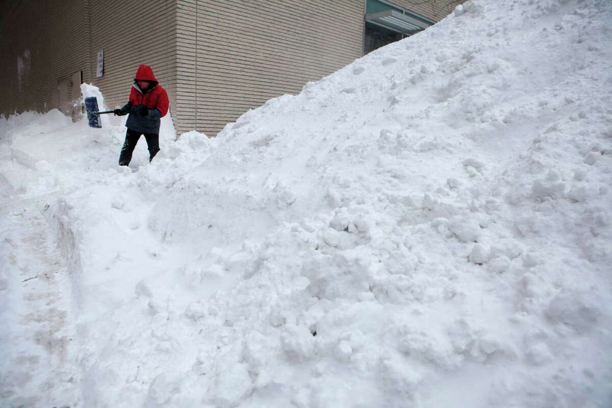 BOSTON, MA - JANUARY 28: Workers continue snow removal efforts in the Back Bay neighborhood the day after Winter Storm Juno, on January 28, 2015 in Boston, Massachusetts. The storm brought 24.4 inches of snow to Boston, and up to 36 inches in other parts of Massachusetts. (Photo by Kayana Szymczak/Getty Images) *** BESTPIX ***