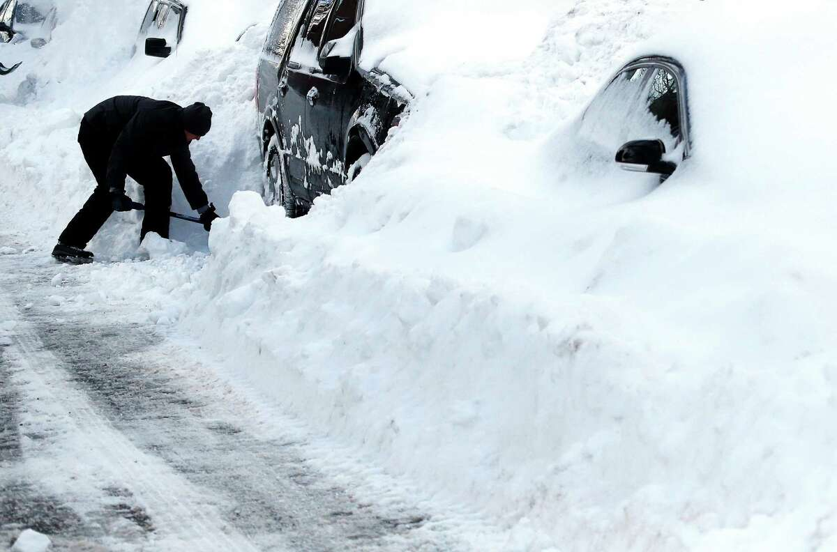 Max Gomez shovels his vehicle out at his home in Boston's Charlestown section, Wednesday, Jan. 28, 2015, one day after a blizzard dumped about two feet of snow in the city. The storm buried the Boston area in more than 2 feet of snow and lashed it with howling winds that exceeded 70 mph. (AP Photo/Elise Amendola)