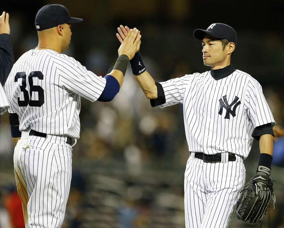 NEW YORK, NY - AUGUST 06: Carlos Beltran #36 and Ichiro Suzuki #31 of the New York Yankees high five each other after defeating the Detroit Tigers 5-1 in a MLB baseball game at Yankee Stadium on August 6, 2014 in the Bronx borough of New York City. (Photo by Rich Schultz/Getty Images) ORG XMIT: 477587497 Photo: Rich Schultz / 2014 Getty Images