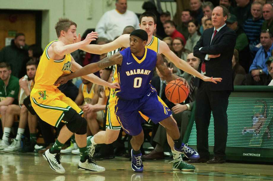 UAlbany guard Evan Singletary looks to pass the ball while being guarded by Vermont guard Cam Ward, left, and Vermont forward Drew Urquhart during their men's basketball game at Patrick Gym on Wednesday, Jan. 28, 2015, in Burlington, Vt. (Brian Jenkins / Special to the Times Union)