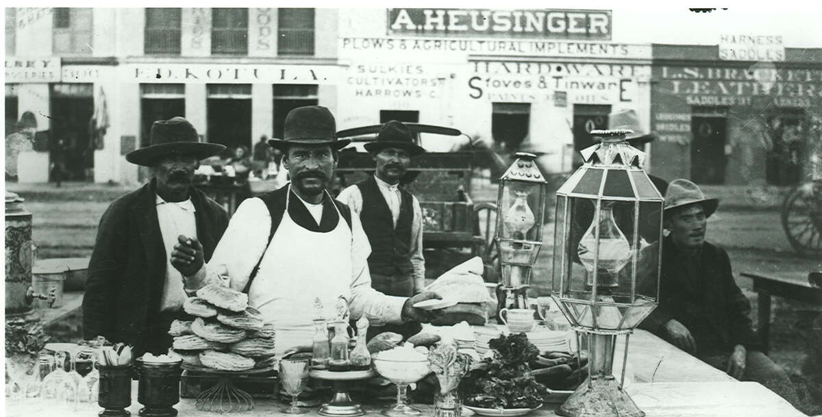 Men work in a chili stand on Military Plaza. Stores owned by Ed Kotula, A. Heusinger and L.S. Brackett, located on south side of plaza, are visible in background in this photo circa 1887-1890.