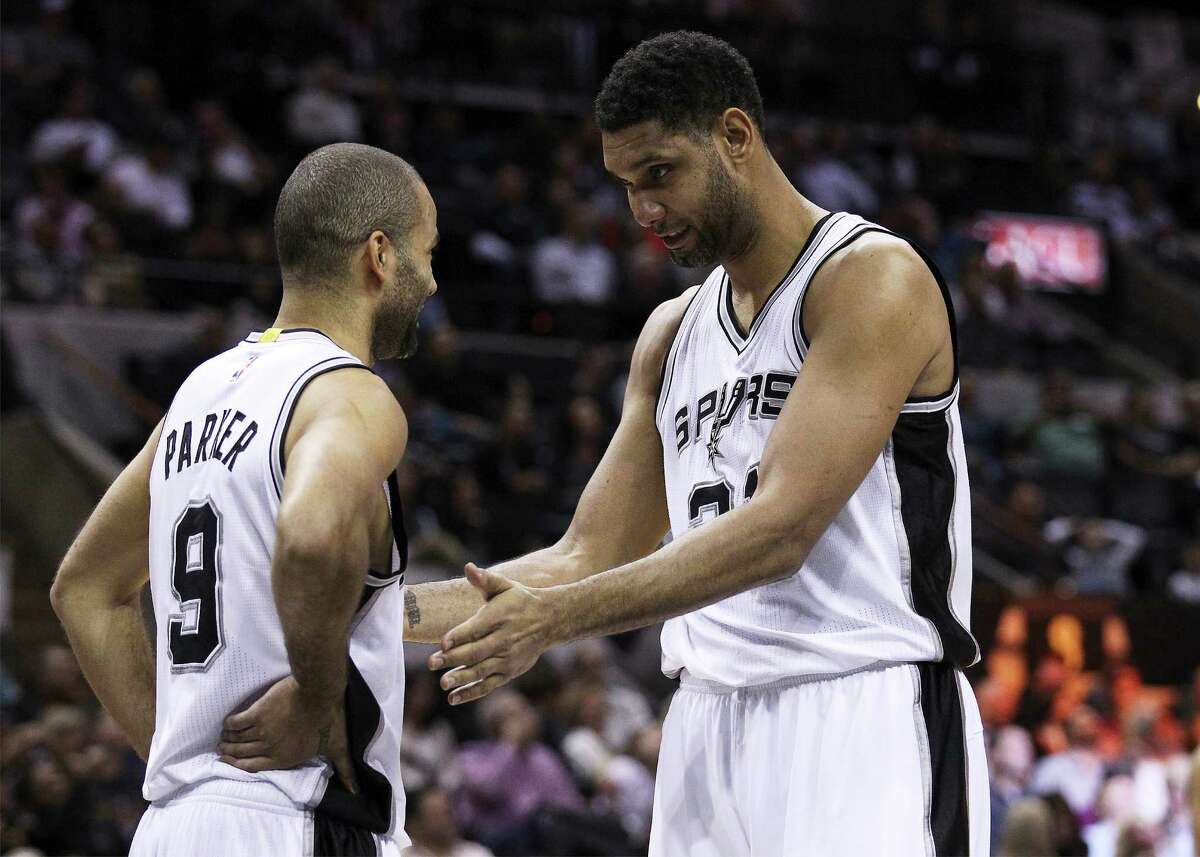 Spurs' Tim Duncan (21) and Tony Parker (09) chat during a timeout against the Charlotte Hornets at the AT&T Center on Wednesday, Jan. 28, 2015. (Kin Man Hui/San Antonio Express-News)