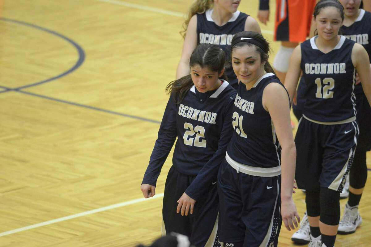 Amber Vidal (22) and Brianna Kallead of O'Connor leave the court after defeating Brennan in District 27-6A girls basketball action at the Paul Taylor Field House on Wednesday, Jan. 28, 2015.