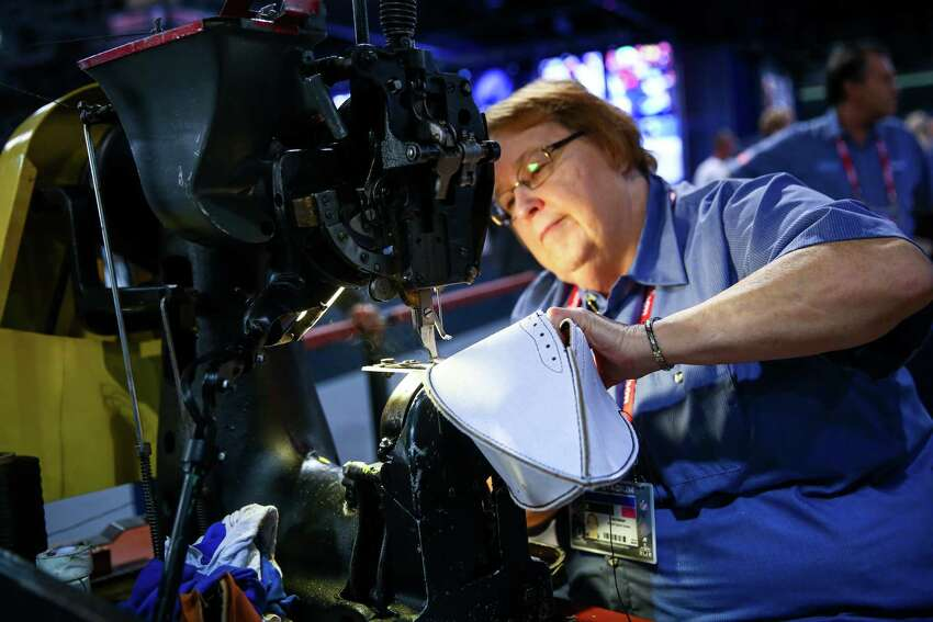 Iva Helser, who worked in the Wilson factory for 48 years, uses an industrial sewing machine to make a football during the NFL Experience on Wednesday, Jan. 28, 2015 in downtown Phoenix. The event is a free, football-themed event for fans. One million visitors are expected to attend Super Bowl-related events in downtown Seattle.