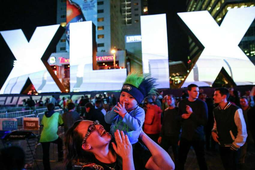 Arielle Fox, originally from Seattle, and her son, Taj Khader, 7 months, have fun at the kickoff of Verizon Super Bowl Central on Wednesday, Jan. 28, 2015 in downtown Phoenix. Super Bowl Central is a free, football-themed outdoor event for fans. One million visitors are expected to attend Super Bowl Central.