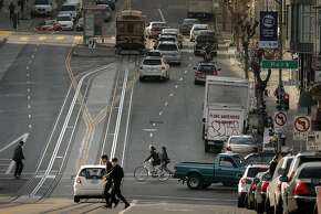 A bicyclist rides through the intersection of Polk and California Streets in San Francisco, Calif., on Wednesday, January 28, 2015. Polk Street improvements might make the narrow street tougher to negotiate as the improvements are designed to make this well traveled bike corridor safer.