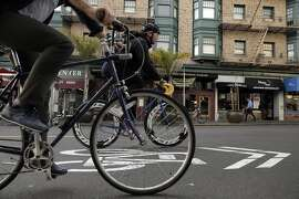 Bicyclists ride their bikes on Polk Street near California Street in San Francisco, Calif., on Wednesday, January 28, 2015. Polk Street improvements might make the narrow street tougher to negotiate as the improvements are designed to make this well traveled bike corridor safer.