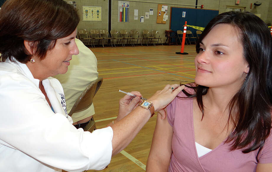 Ariane Balla of Fairfield gets a flu shot from nurse Mary Ellen Dragicevich at a town clinic in the Fairfield Senior Center. Photo: Mike Lauterborn / Fairfield Citizen contributed