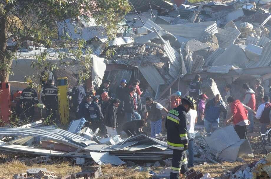 Socorristas trabajan entre los escombros causados por la explosión de un camión cisterna de gas en Cuajimalpa, en la capital mexicana, el 29 de enero 2015. El periódico mexicano El Universal reporta cuatro bebés y tres adultos muertos por el estallido. Photo:  David Deolarte, AFP / Getty Images