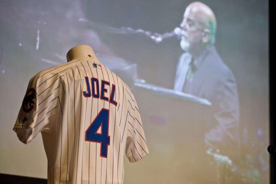 Billy Joel es un confeso apasionado del baseball y, aunque es de Nueva York, y en esta fotografía el equipo Cachorros de Chicago, durante un concierto en la ciudad de los vientos, le regaló un jersey con su nombre. Photo: Timothy Hiatt, Getty Images