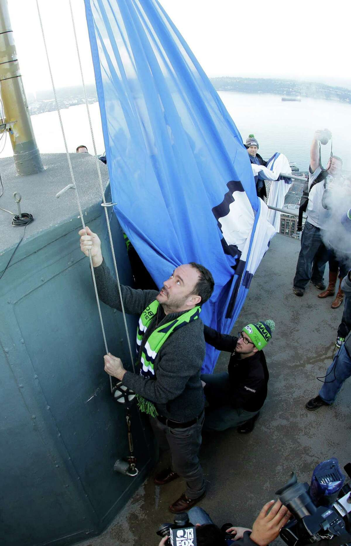 In this photo taken with a fish-eye lens, musician Dave Matthews, left, raises the Seattle Seahawks 12th Man flag on Thursday on the roof of the Space Needle.