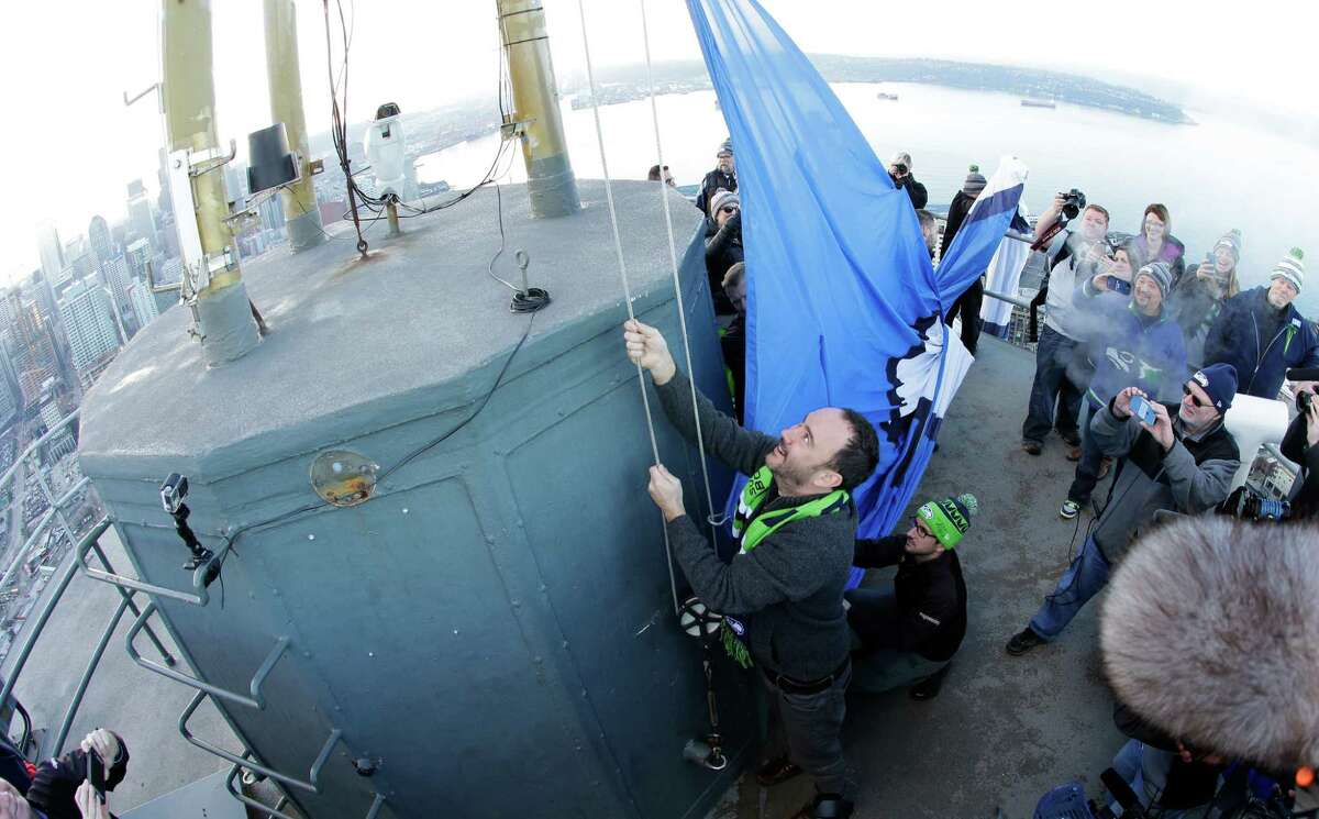 In this photo taken with a fish-eye lens, musician Dave Matthews, left, raises the Seattle Seahawks 12th Man flag on Thursdayon the roof of the Space Needle.