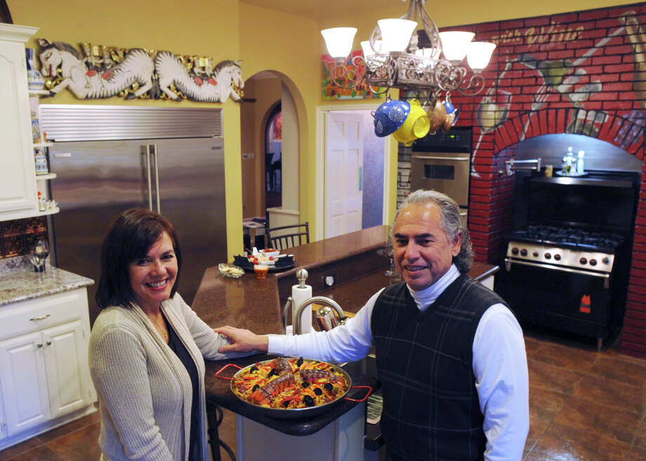 Al (with his beloved paella nearby) and Patsy Molinar enjoy entertaining friends and family. They're originally from El Paso. Photo: Billy Calzada / San Antonio Express-News / San Antonio Express-News