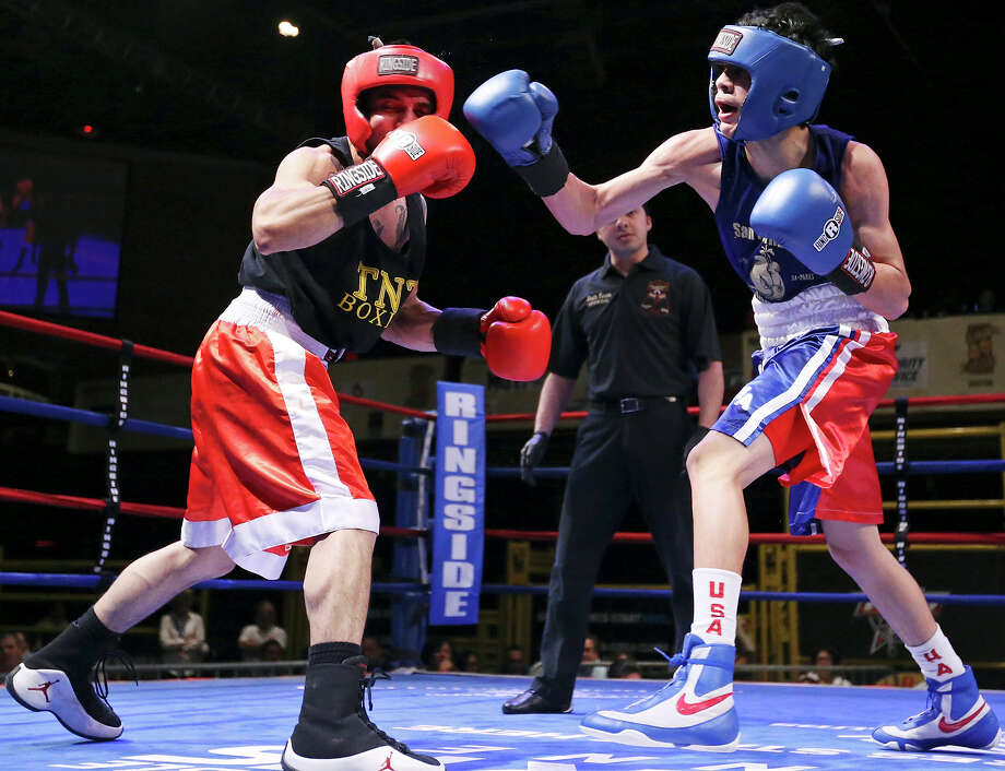 Ramon Castro (left) is hit by Hector Tanajara during their open bantamweight bout at the San Antonio Regional Golden Gloves tournament on Feb. 22, 2014 at Cowboys Dancehall. Photo: Edward A. Ornelas /San Antonio Express-News / © 2014 San Antonio Express-News