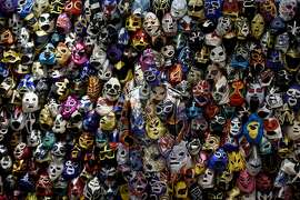 Chinese artist Liu Bolin (center) stands during a performance with masks in  the lobby of the Presidente Intercontinental Hotel in Mexico City on January 28, 2015.