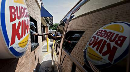 Bloomberg Photo Service 'Best of the Week': An employee assists a customer at the drive-through of a Burger King Worldwide Inc. restaurant in Peoria, Ill